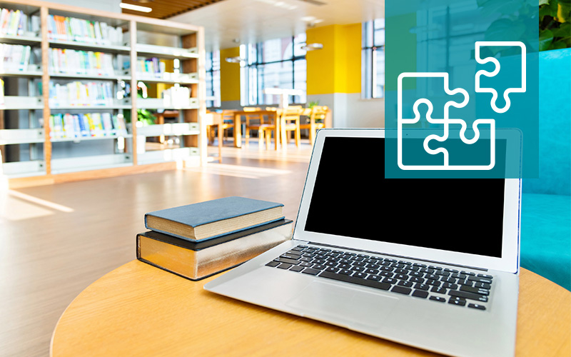 Image of computer and books in library