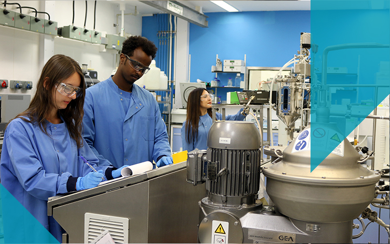 3 scientists in pilot plant blue lab coats