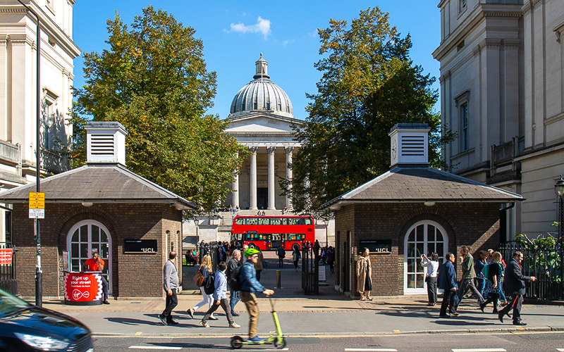red bus in front of UCL Portico