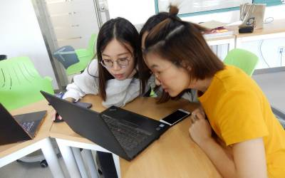 two_female_students_with_laptop