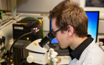 man examining item under microscope