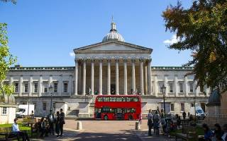 Main campus of UCL. There is a large red bus parked in front of the main building.