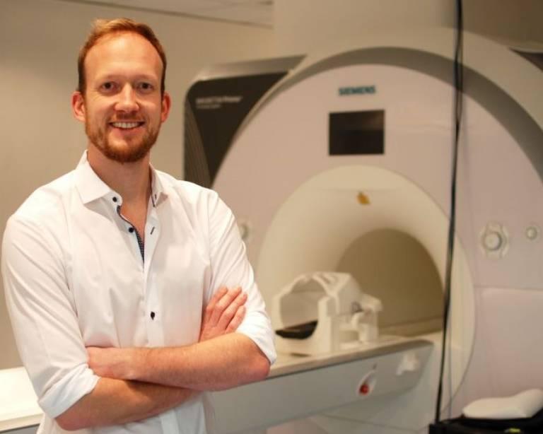 Tobias Hauser standing next to an MRI machine