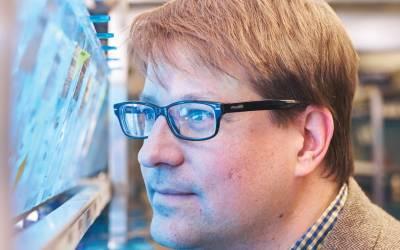 Jason Rihel looks at fish tank