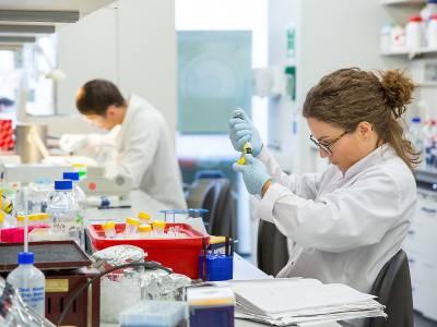 Researcher using microscope…