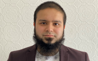 Picture of Imran Uddin, Imran has short dark hair and a beard and is in front of a white background.