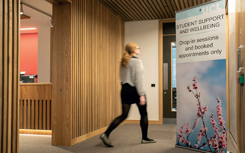 Student support and success. Image of a women walking in front of a sign for student wellbeing and support