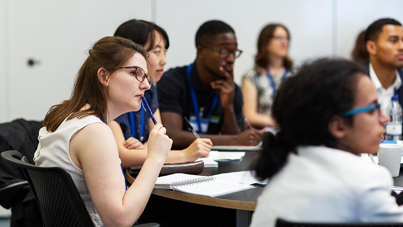 Students sat around a desk listening to a speaker