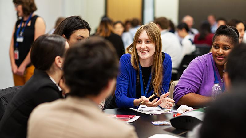 Students around a desk talking