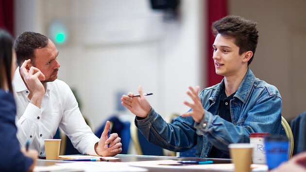 Student expressing himself with hand motions while interviewer looks on