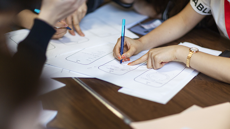 A close up of students planning on a large sheet of paper on a table