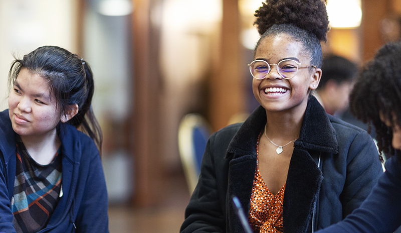 Student sat at desk with other students smiling