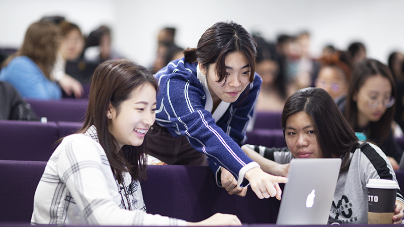 Three students in a lecture theatre, one of them is pointing at a screen