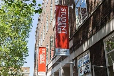 Image of the outside of the Student Central building, with red student central banners on the building