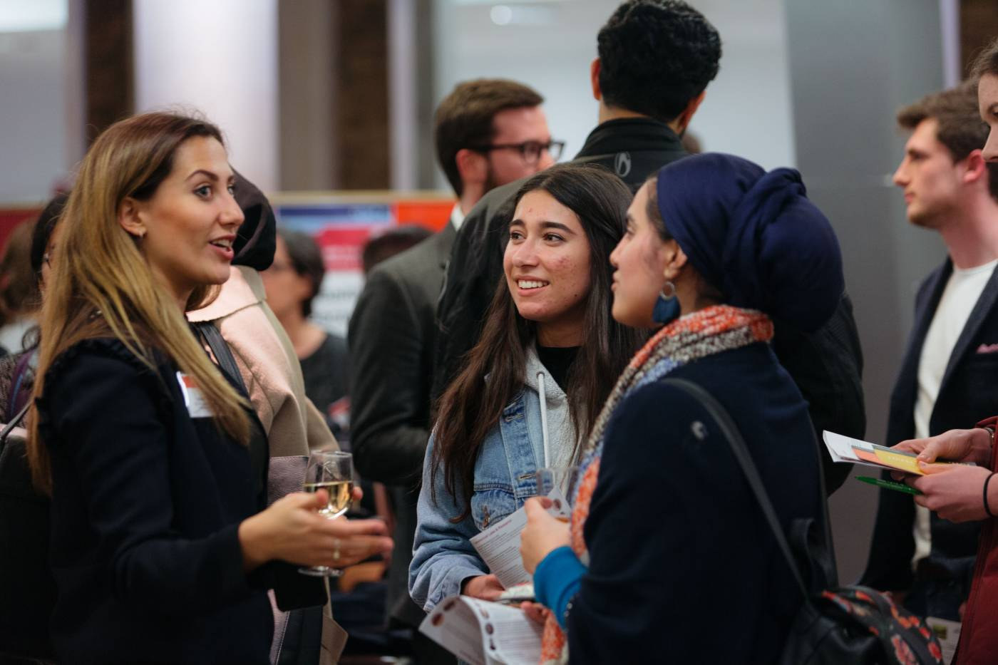 Two students standing talking to an employer at a careers fair