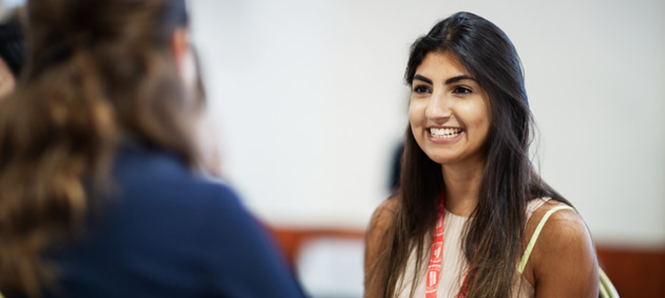 young woman smiling at someone blurred by the camera