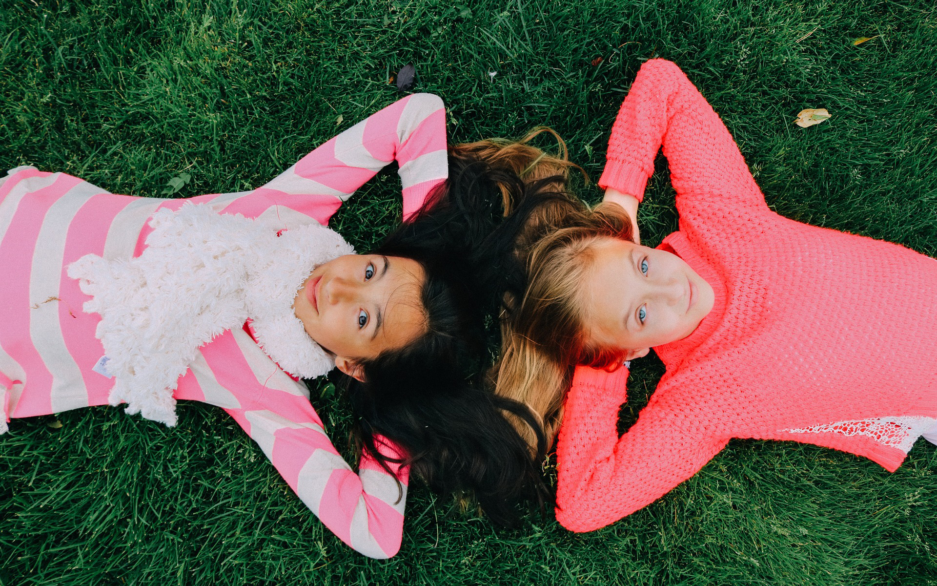 Two girls lying on their back looking up at the sky