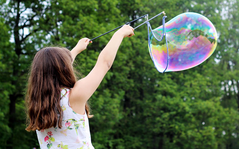A young girl outside blowing bubbles using a kit
