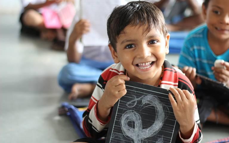 A boy smiling holding a chalkboard
