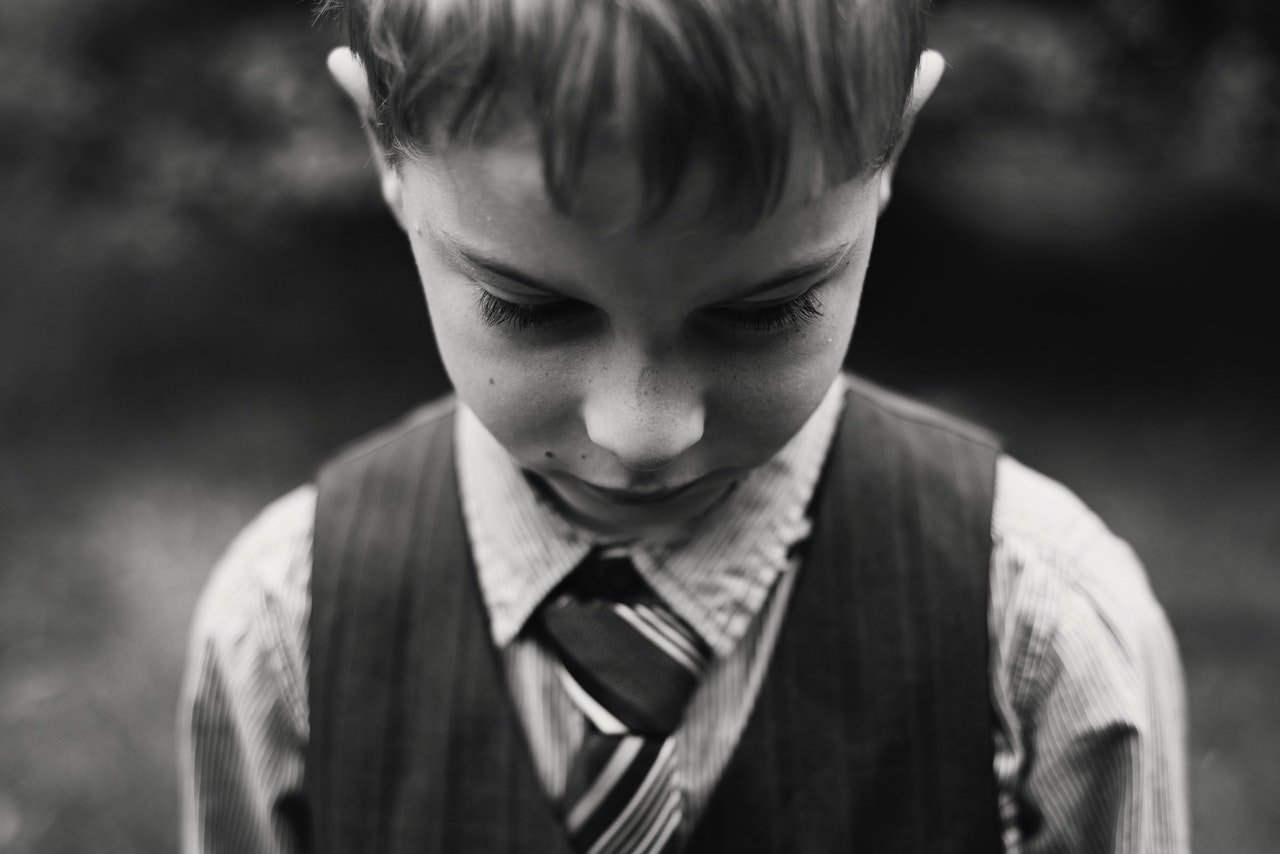 Black and white head shot of boy looking sullen