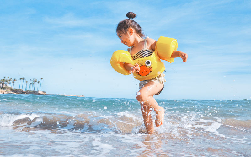 A girl on a beach wearing armbands