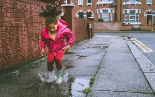 Little girl in pink raincoat and wellies jumping in puddle