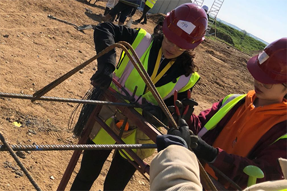 Two civil engineering students tying steel reinforcement bars