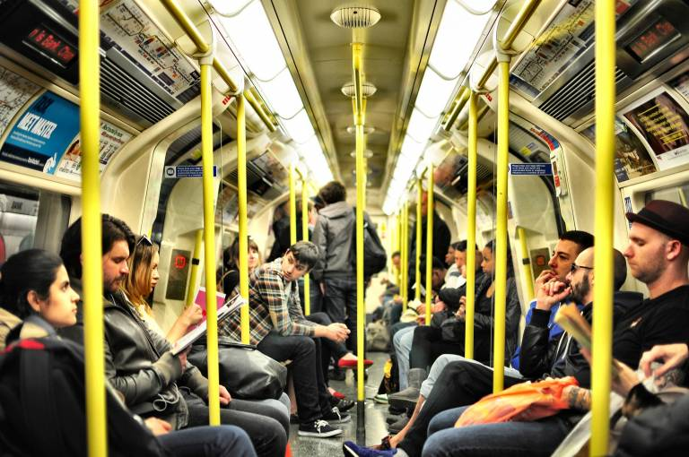 A shot of a London Underground tube carriage with people sat down, reading and looking round.