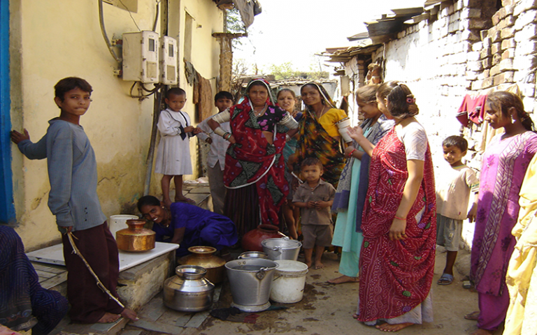 Women and children collecting water from a communal tap in India