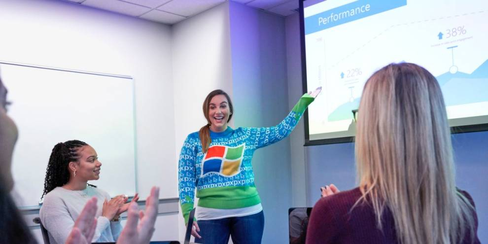 Young girl wearing MS Windows logo sweater presenting in a classroom for a group of people
