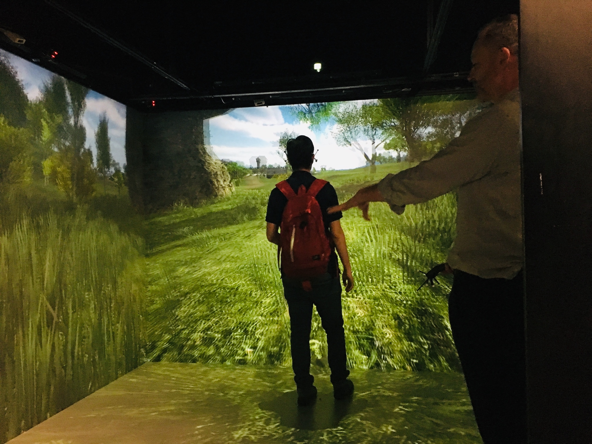 Student wearing backpack using virtual reality cave  displaying an open field landscape with tutor pictured to the side.