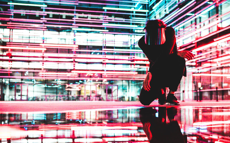 A crouching person in a brightly lit, multicoloured room