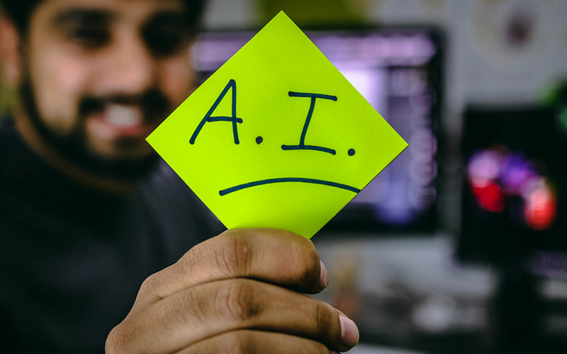 A man holding up a post-it to the screen that reads AI