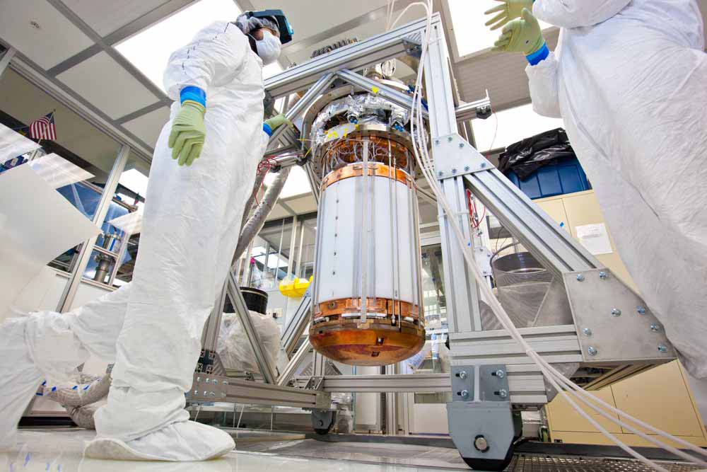 LUX researchers, seen here in a clean room on the surface at the Sanford Lab, work on the interior of the detector, before it is inserted into its titanium cryostat, Lawrence Livermore National Laboratory…
