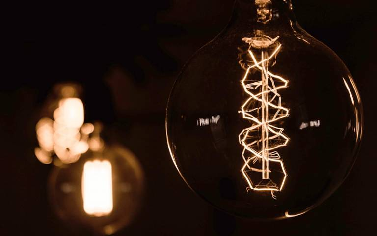 A close up of a lightbulb showing a DNA-style filament