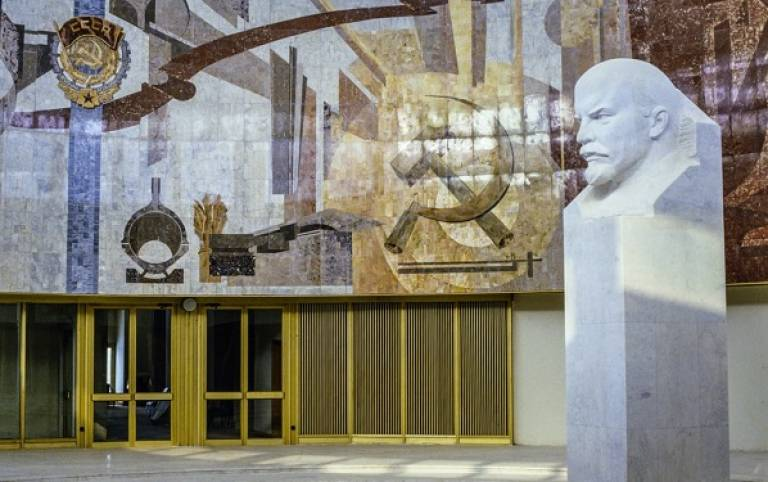In the right hand side of the forefront of the photograph there is a bust of Lenin made of white stone. Behind there is a building with big yellow doors and above this a mosaic with the hammer and sickle in shades of blue, yellow and brown.