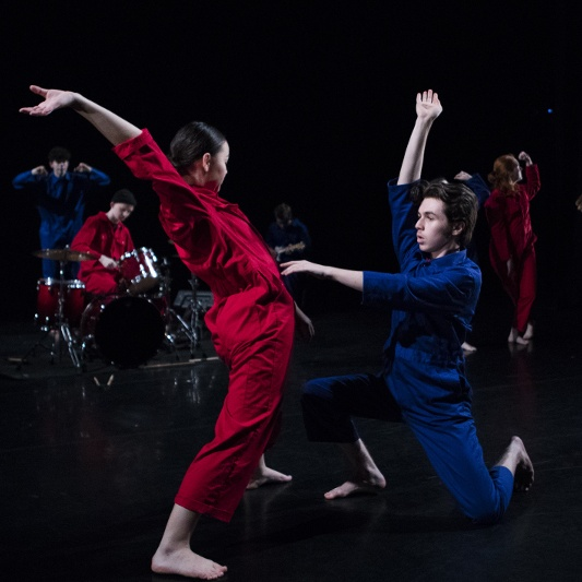 Colour photo of two dancers on stage, one in a red jumpsuit and the other in a blue one