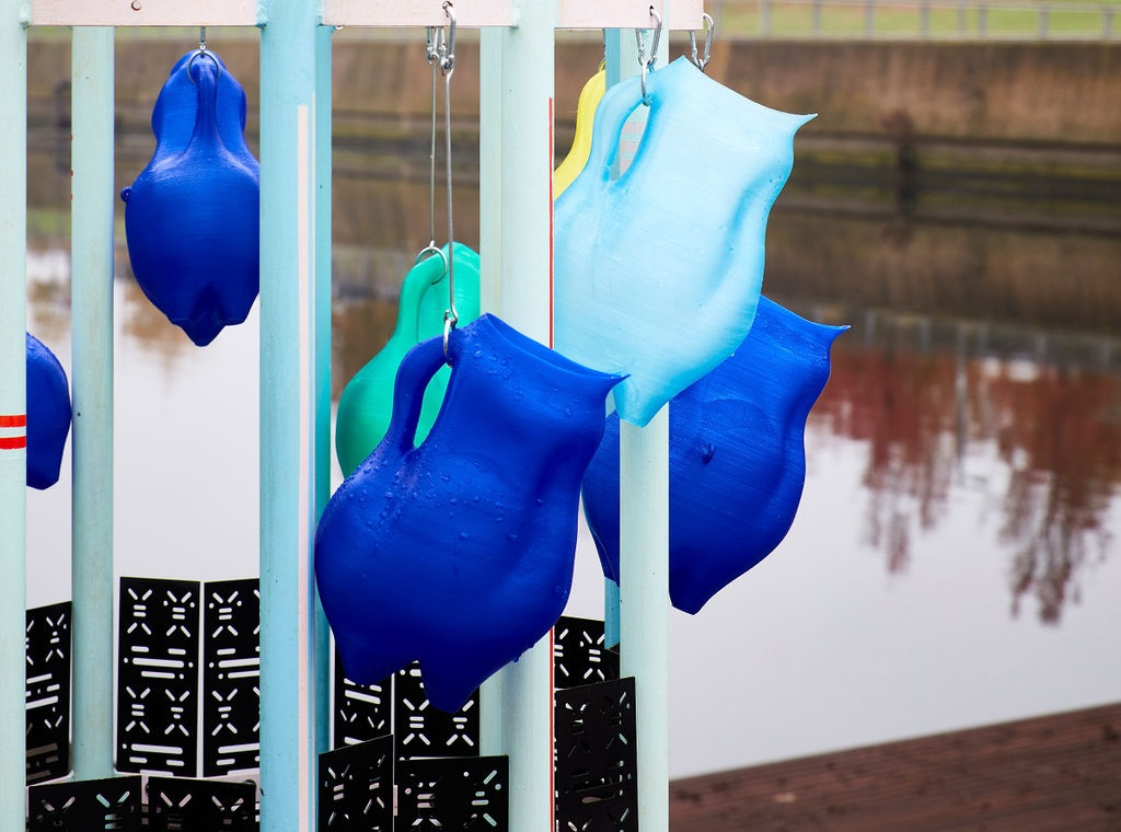 different shades of blue jug hanging from a metal structure, next to water