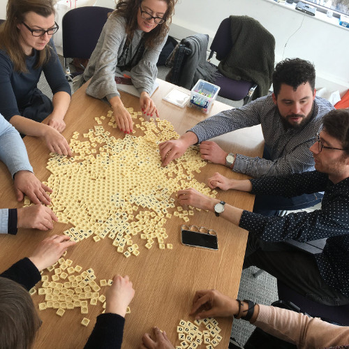 People around a table playing scrabble