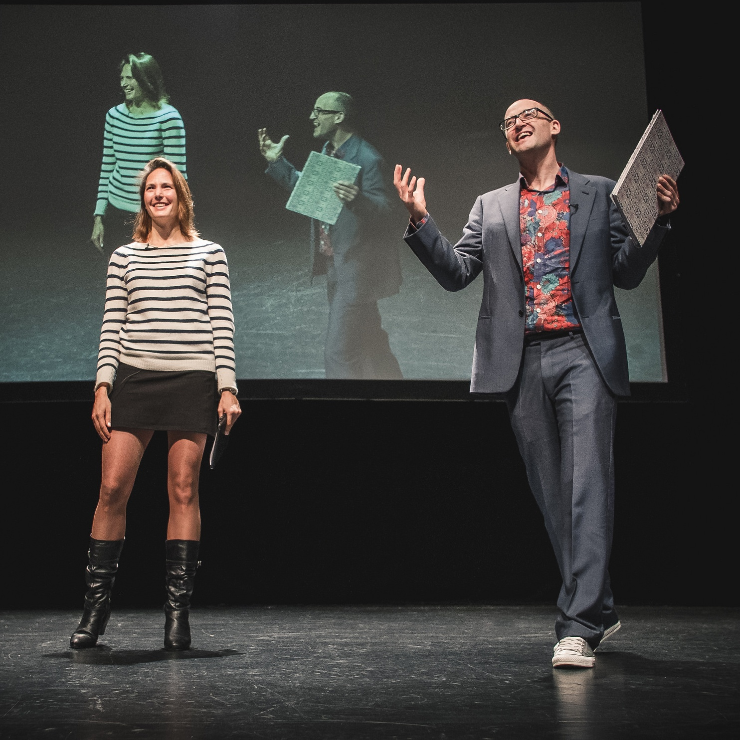 Colour photo of two people standing on a stage