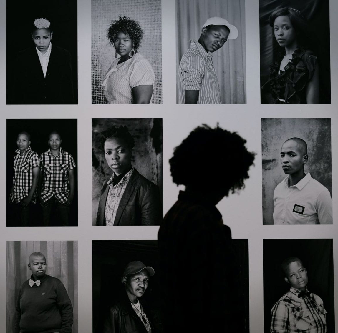 Image is a collage of photographs hung on the wall, showing a diverse group of black people with a person walking past and looking at it. Image credit: Christian Fregnan, Stedelijk Museum Amsterdam