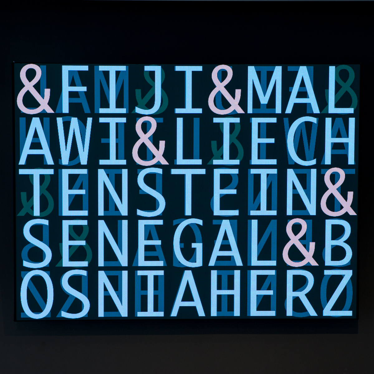 Colour photo of a digitial screen with large blue letters spelling out FIJI & MALAWI & LIECHTENSTEIN & SENEGAL & BONSNIA HERZ