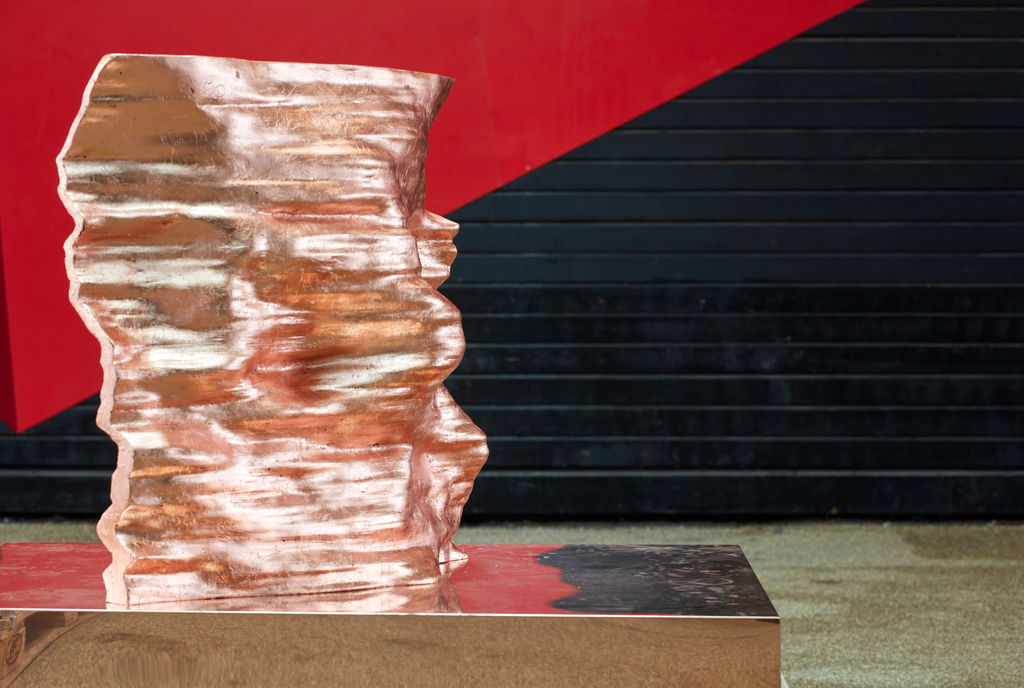Copper sculpture with undulating surface, in front of red and black wall