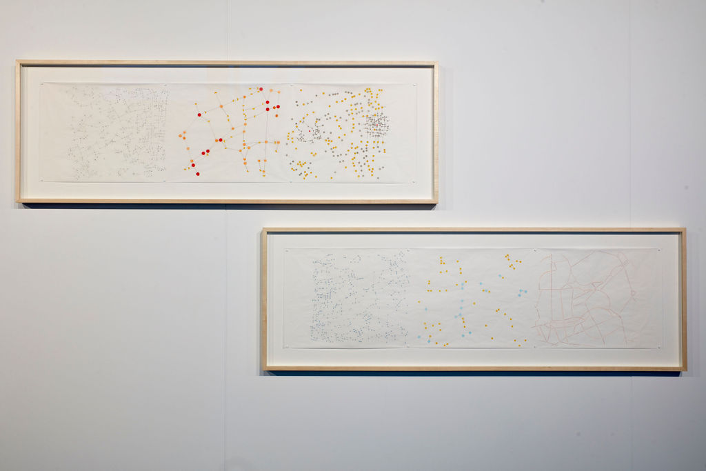 two landscape picture frames on a while wall. inside are abstract maps made of dots and lines in red and yellow