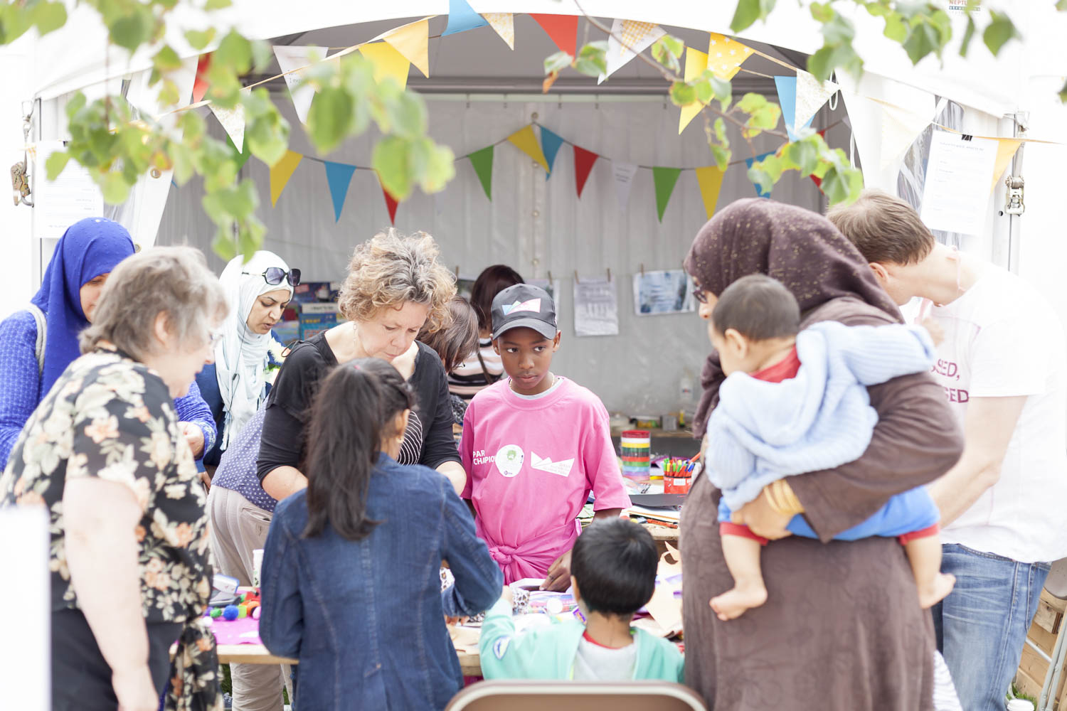 Families taking part in an activity at a festival stall