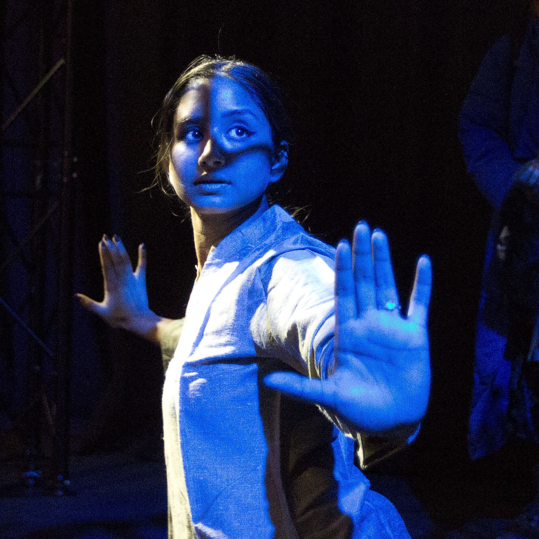 Female performer with arms outstretched under a blue light