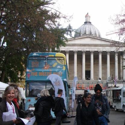 Colour photo of the main UCL building. People are walking in frount, alongside a brightly coloured bus