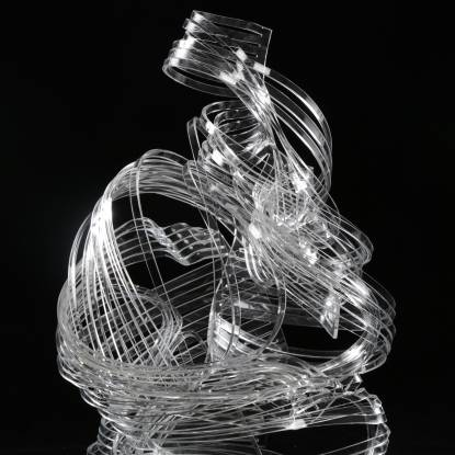 Colour photo of a sculpture, made of clear, thin strands of plastic which are tangled against a black background