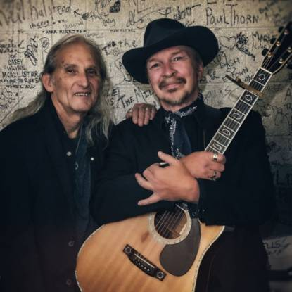 Dave Alvin & Jimmie Dale Gilmore wearing black suits, standing in front of a graffitied wall
