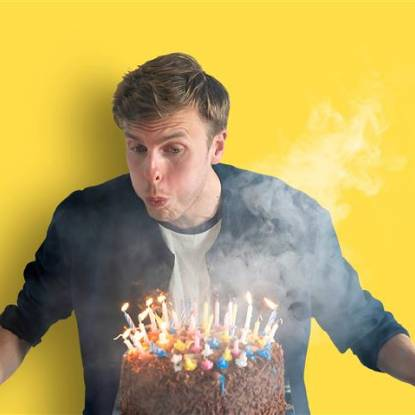 Harry Baker blowing out a candle against a yellow background